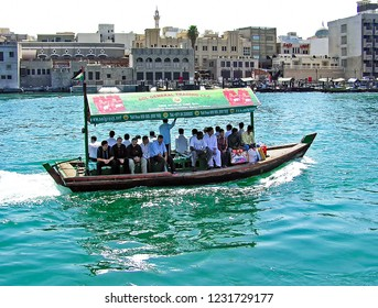 Dubai, United Arab Emirates - July 5, 2004: People cross the Dubai Creek between the districts of Deira and Bur Dubai aboard a traditional Abra water taxi.
