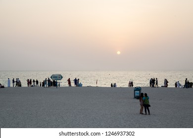 Dubai, United Arab Emirates - July 20, 2018: Crowd of people at Jumeirah Public Beach on a Friday evening during sunset