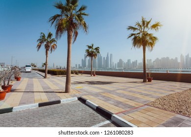 Dubai, United Arab Emirates - June, 2018. Buildings, street, sunny day, palm trees. Skyscrapers at Dubai Marina Promenade