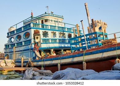 DUBAI, UNITED ARAB EMIRATES - March 19, 2018: Street photography c in Old Dubai with tipical wooden boats connecting both banks and  the ancient covered textile souq Bur Dubai in the old city centre.