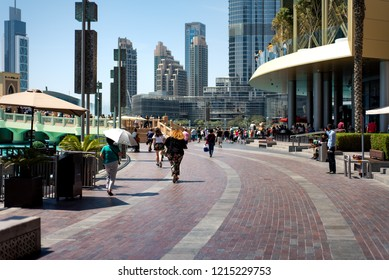 Dubai, United Arab Emirates - March 26, 2018: Tourists running to see Dubai mall fountain show at day time