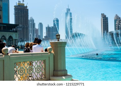 Dubai, United Arab Emirates - March 26, 2018: People gather around the Dubai mall fountain to see the water show which attracts many tourist every day