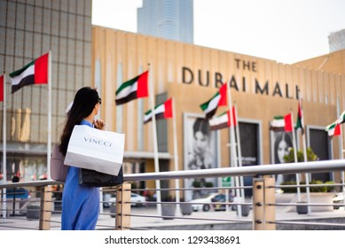 Dubai, United Arab Emirates - March 26, 2018: Asian tourist in front of Dubai mall main entrance with shopping bags