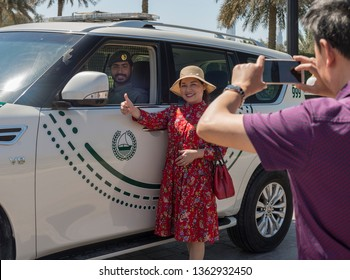 Dubai / United Arab Emirates - March, 2019: Tourists photograph themselves on the background of smiling guard of the palace of the sheikh