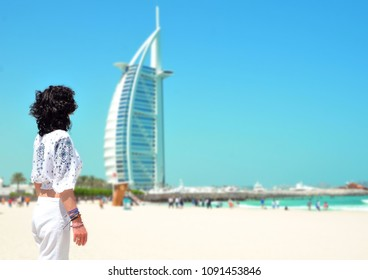 DUBAI, UNITED ARAB EMIRATES - MAY 2017 : Woman in front of Burj Al Arab, famous landmarks of United Arab Emirates seen from public beach.