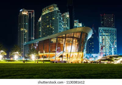 Dubai, United Arab Emirates - May 18, 2018: Dubai opera building and modern skyscrapers of the Dubai mall surroundings at night