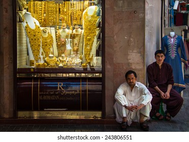 DUBAI, UNITED ARAB EMIRATES - MAY 20, 2013: 2 merchants in front of gold shop in Gold Souk, Dubai.