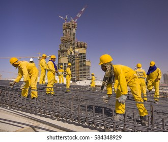 DUBAI, UNITED ARAB EMIRATES - MAY 7, 2006: South Asian immigrant contract laborers from Bangladesh, India, and Pakistan work at the construction site of Burj Khalifa, on Sheikh Zayed Road.
