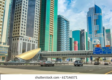 Dubai, United Arab Emirates - May 1, 2013: Dubai Financial Centre Metro station and footbridge. Underground lines without driver in the Dubai metro. Traffic on Sheikh Zayed Road, the highway E 11.