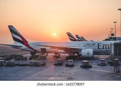 Dubai, United Arab Emirates - Noveber 8, 2016: Emirates Airline planes in a row being prepared to fly. Airport morning sunrise.