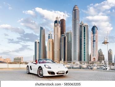 Dubai, United Arab Emirates  - November 1th, 2013: White Porsche Cayman against the background of skyscrapers.
