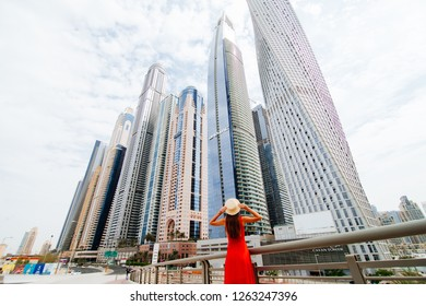 Dubai, United Arab Emirates - October, 2018: Rear view of young woman in red dress holding with both hands straw hat amazed looking up on skycrapers at downtown in modern city.
