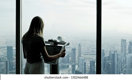 Dubai, United Arab Emirates  - October 31, 2018: A young woman is standing on the indoors observation deck of the high Burj Khalifa skyscraper in Dubai and looking over the downtown district.