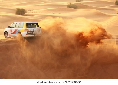 DUBAI, UNITED ARAB EMIRATES - October 15, 2014 - Driving through the sand dunes and kicking up dust