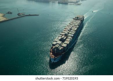 Dubai, United Arab Emirates - October 17, 2014: Aerial view of a cargo container ship leaving the harbor