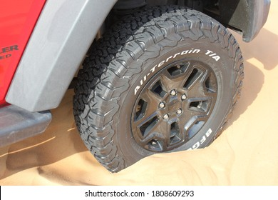 Dubai, United Arab Emirates - September 4, 2020: All-terrain tire on a Jeep Wrangler 4x4/SUV in desert sand dunes. Tire is deflated to low pressure to provide extra traction in the soft desert sand.