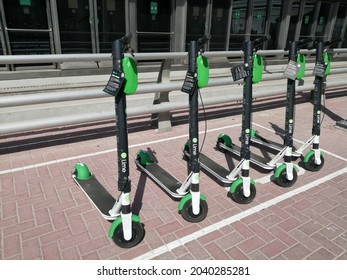Dubai, United Arab Emirates - September 12, 2021: Lime electric scooter (e-scooter) available for rent via payment on an app accessible by a smartphone with internet access. Micromobility concept.