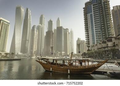 DUBAI, UNITED ARAB  EMIRATES - SEPTEMBER 13, 2017: Traditional Wooden Boat and Skycrapers in Dubai Marina, Western Dubai