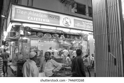 DUBAI, UNITED ARAB EMIRATES - SEPTEMBER 6, 2015: Inexpensive cafe with people in dirty streets in the Dubai Nasser square after the hard working day