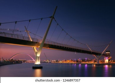 Dubai, United Arab Emirates (UAE). Two pedestrian bridge over the water channel and reflections of street lights in the evening. In the background, Tolerance Bridge