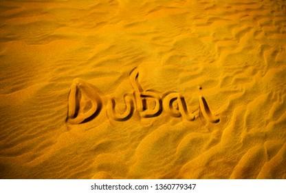 Dubai word in sand desert travel concept