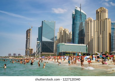 Dubai,UAE / 10.31.2018 : crowded JBR Jumeirah beach with tourists enjoying the sun and the sea with skyscapers in the background