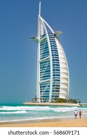 DUBAI,UAE - MARCH 12,2012:Hotel Burj al Arab on the beachfront, the girl with the guy walking next to him.