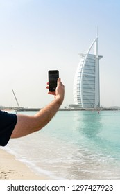 Dubai/UAE-CIRCA 01.2019: an image of a man from his back, wearing dark t shirt, taking a photograph on his phone, off a skyscraper on the urban beach