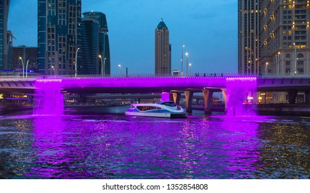 Dubai-United Arab Emirates, 3/22/2019, Water Canal Bridge Dubai Famous attraction of Middle UAE, RTA boat pass through colorful illuminated water fountain place to visit