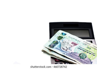 Dubai,United Arab Emirates currency banknotes and calculator ready for exchange and business investment,Focus on eye of hawk on top banknote with copy space