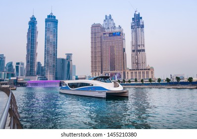 Dubai/United Arab Emirates-7/12/2019 - Dubai RTA Ferry Boat Service through Business bay Water Canal bridge stunning view of  Skyline Buildings and tolerance bridge