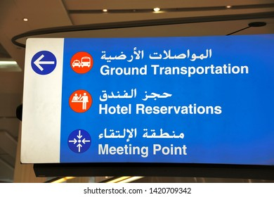 DUBAI,UNITED ARAB EMIRATES-FEBRUARY 07, 2014: Sign in English and Arab at Dubai airport indicating the way to the ground transportation, the hotel reservations and the meeting point.