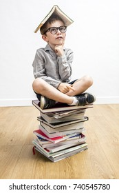 dubious 6-year old schoolboy with smart eyeglasses with a book on his head having learning questions seated on top of a pile of books on white background and wooden floor