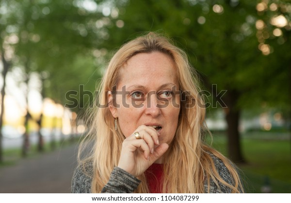 Dubious woman with her hand in her mouth