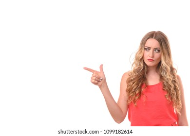 Dubious young woman pointing to the side to blank copy space with a worried frown unable to reach a decision isolated on a white studio background