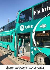 Dublin Airport, Ireland - February 2018: Wide angle view of an Airlink shuttle bus with its door open  and another bus in the background. The buses run to and from the city centre