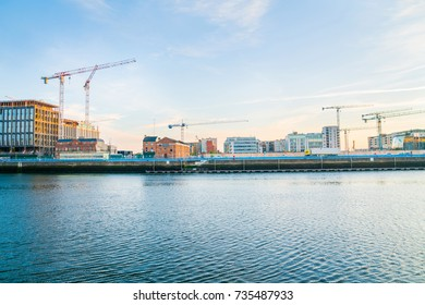 Dublin building boom illustrated in early morning image across Liffey River an array of old wharf, modern newer, and under construction buildings with construction cranes across skyline. Ireland.