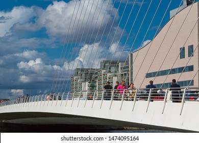 Dublin, Docklands / Republic of Ireland - August 2019 - Sunny day in Dublin during rush hours. People walking on Samuel Beckett bridge