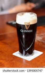 DUBLIN, IRELAND- 19 April 2019: Pint of Guinness on Wooden Pub Table