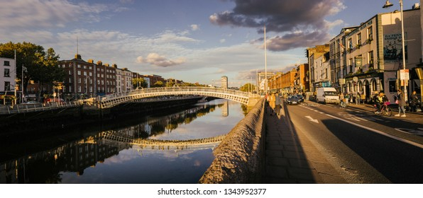 Dublin, Ireland - 24.09.2018. Amazing panoramic view of Ha Penny Bridge above tranquil river water in vibrant sunset light above city