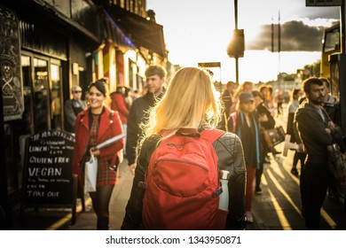 Dublin, Ireland - 24.09.2018. Back view of blond woman with backpack walking in crowd on city waterfront in golden sunset light