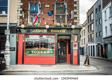 Dublin, Ireland - 24.09.2018. Facade of James Toner bar window with colorful flag garland above on empty street in daylight