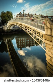 Dublin, Ireland - 24.09.2018. Perspective view of calm Liffey river with people walking on Ha Penny Bridge in bright sunset light