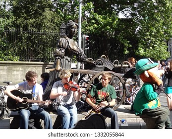 Dublin, Ireland - 3 August 2012: Irish boys busking beside the Molly Malone statue with someone dressed as a Saint Patrick sitting beside them