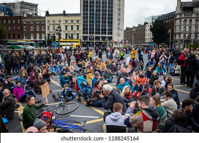 Dublin, Ireland _ September 22nd 2018. Protest over housing in Dublin on O'Connell Bridge in Dublin. People sitting in the street and signing song.