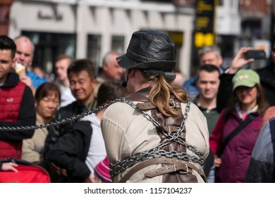 Dublin, Ireland - April 18 2017: A street entertainer / escape artist tries to escape from strait jacket and chains, watched by a crowd of people.