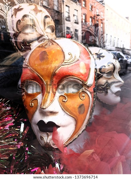 DUBLIN, IRELAND - APRIL, 2019: Vertical shot of colorful carnival masks in shop window.