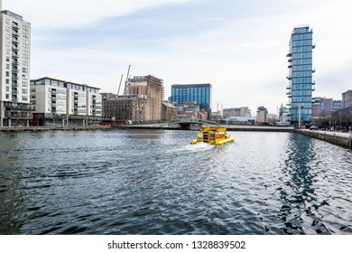 DUBLIN, IRELAND - APRIL 21, 2016: Cityscape view seen from the waters edge with a yellow tourist cruise boat / vehicle in the center of Dublin Ireland April 21, 2016.