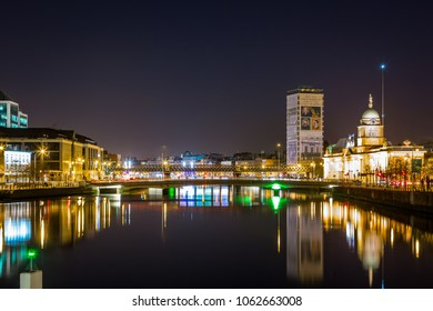 DUBLIN, IRELAND - APRIL 22, 2016: Night view seen from the river with water, bridge and buildings in the center of Dublin Ireland April 22, 2016.