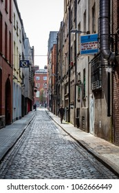 DUBLIN, IRELAND - APRIL 22, 2016: Narrow industrial street with cobblestone, signs and incidental people in the old parts of  Dublin April 22, 2016.